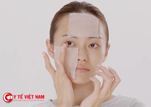 Sử dụng giấy thấm dầu để loại bỏ dầu thừa trên gương mặt